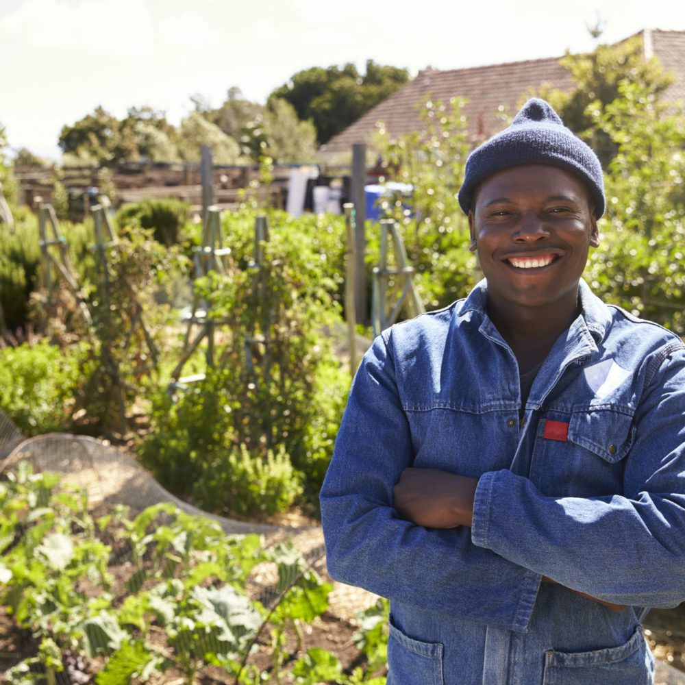 Portrait Of Gardener Standing In Community Allotment
